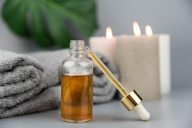 Asciugamano con candele aromatiche, bottiglia con oli essenziali biologici naturali
