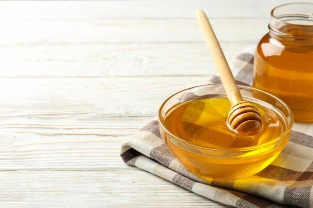 Asciugamano con ciotola e vasetto di miele e mestolo su fondo di legno bianco