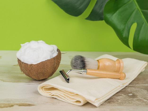 Un asciugamano con accessori per la rasatura e una ciotola con schiuma di cocco.
