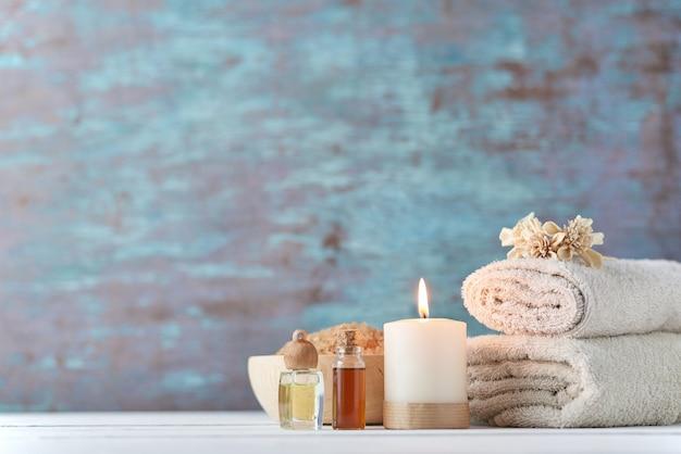 Asciugamani, candele e olio da massaggio sul tavolo bianco