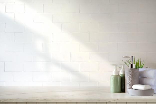 Asciugamani e sciampo o sapone della ceramica sulla tavola di marmo superiore nel fondo del bagno.