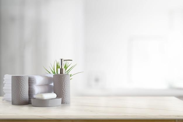 Asciugamani e sciampo o sapone della ceramica sulla tavola di marmo superiore con lo spazio della copia su fondo vago del bagno.