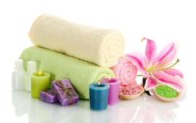 Asciugamani con giglio, olio aromatico, candele, sapone e sale marino su bianco