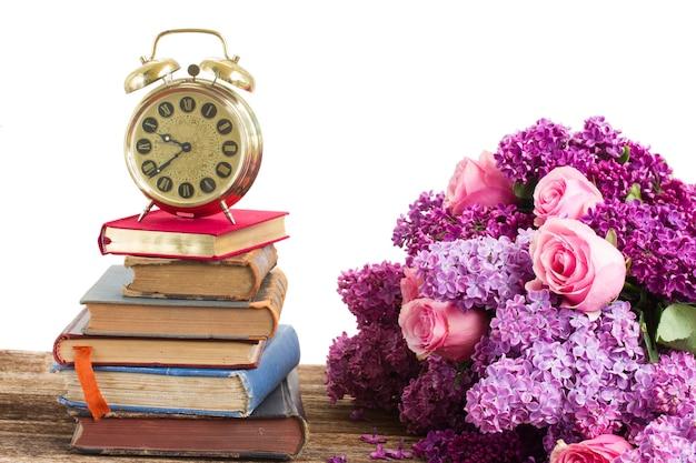 Torre di libri e orologio con fiori lilla e rosa isolati su bianco