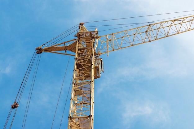 Primo piano della gru a torre su un fondo di cielo blu. costruzione di alloggi moderni. ingegneria industriale. costruzione di abitazioni ipotecarie.