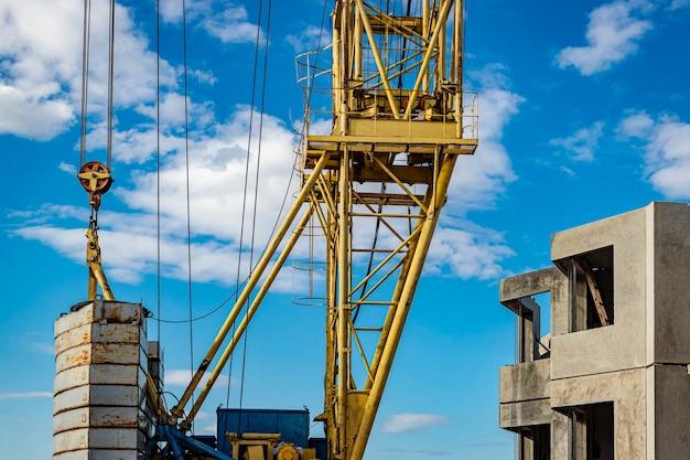 Gru a torre sul primo piano delle rotaie contro lo sfondo del cielo nuvoloso. costruzione di alloggi moderni. ingegneria industriale. costruzione di abitazioni ipotecarie.