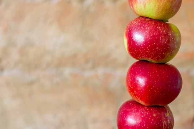 Una torre di cinque mele rosse fresche sui precedenti del muro di mattoni.