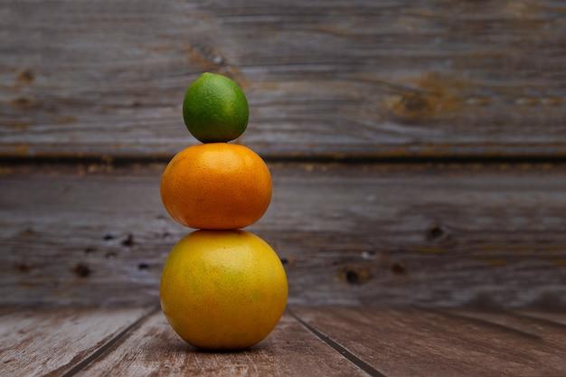 Torre formata da un'arancia, un mandarino e un limone con fondo in legno