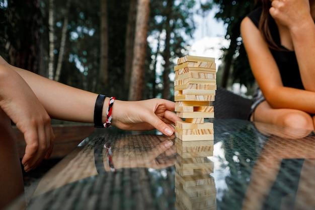 La torre di blocchi di legno e la mano della donna prendono un blocco
