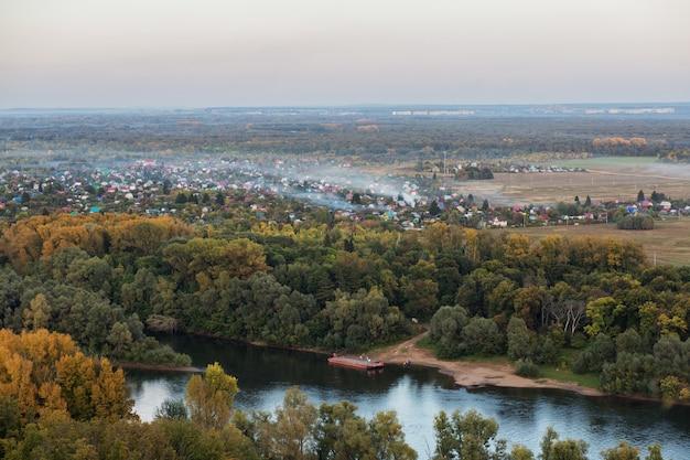 Città nella foresta di autunno in serata nebbiosa