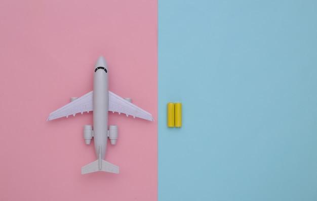 Aereo giocattolo e batterie su uno sfondo pastello blu-rosa. vista dall'alto