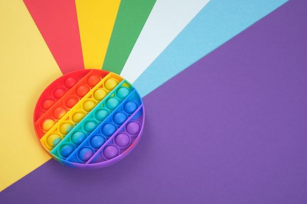 Giocattolo antistress pop su uno sfondo arcobaleno, gioco di fidget, bolle che scoppiano e calmati and