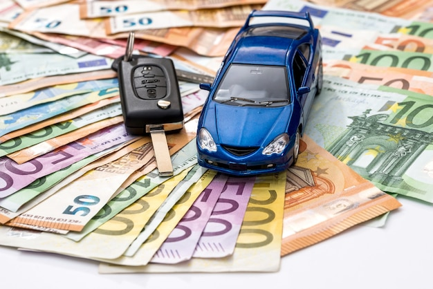 Automobile del giocattolo e chiavi reali sulla superficie delle banconote in euro