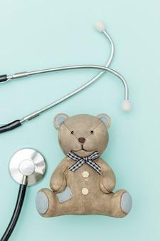 Giochi l'orso e lo stetoscopio dell'attrezzatura della medicina isolato su fondo blu pastello