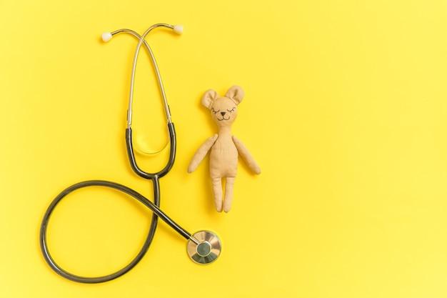 Orso del giocattolo e stetoscopio dell'attrezzatura della medicina isolato sulla tabella gialla