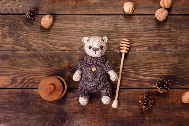 Orso giocattolo legato da fili di lana su un tavolo scuro. lavoro manuale, hobby