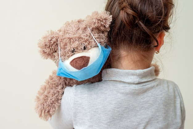 Orso giocattolo con maschera protettiva sulla spalla del bambino