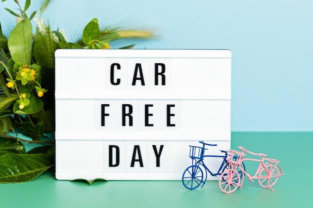 Bicicletta giocattolo e lightbox con giorno senza auto di testo. giornata mondiale della bicicletta, protezione dell'ambiente, concetto di stile di vita sostenibile con spazio di copia