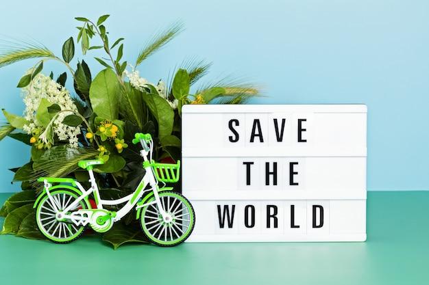 Bicicletta giocattolo e lightbox con testo salva il mondo. giornata senza auto, giornata mondiale della bicicletta, protezione dell'ambiente, concetto di stile di vita sostenibile con spazio per le copie