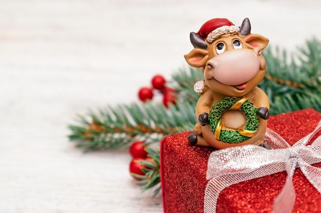 Toro giocattolo in un cappello di babbo natale su una confezione regalo