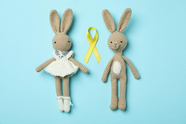 Coniglietti giocattolo e nastro di consapevolezza del cancro infantile su sfondo blu