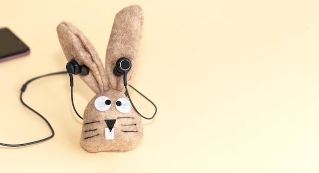 Toy bunny su uno sfondo beige in cuffia. copia spazio.