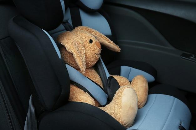 Coniglietto giocattolo seduto nel seggiolino di sicurezza