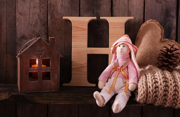 Coniglietto giocattolo con lettera sciarpa di lana e casa su fondo in legno