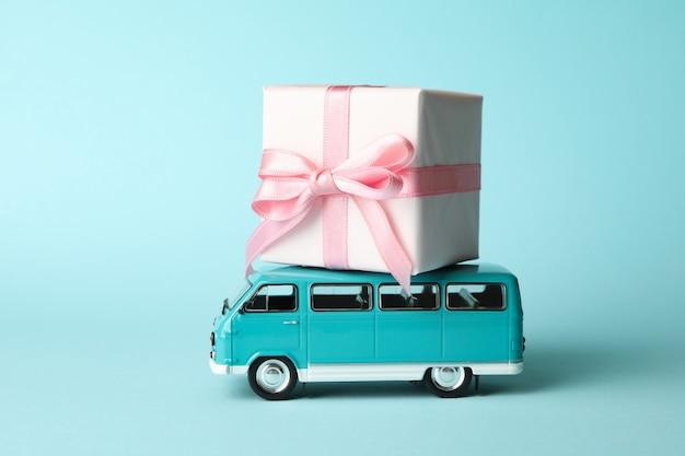 Autobus giocattolo con confezione regalo su sfondo blu