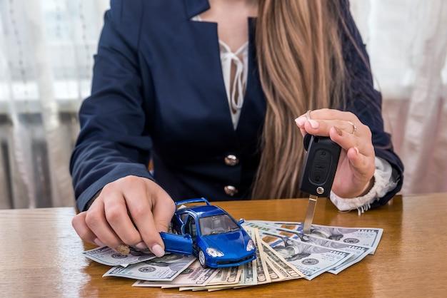 Macchinina e chiavi in mani femminili sulle banconote in dollari