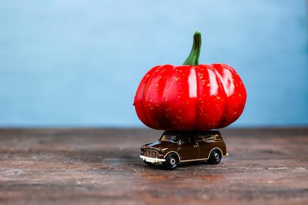 Un'auto giocattolo con una grande zucca arancione concetto di raccolta autunnale