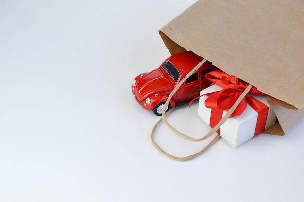 Auto giocattolo con una confezione regalo sul tetto su uno sfondo bianco. minimalismo. giocattoli. il concetto di un regalo per una vacanza, compleanno, natale, pasqua. copia spazio