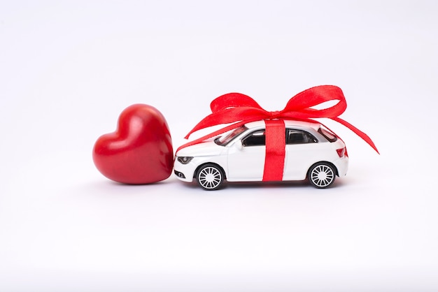 Automobile del giocattolo con cuore rosso dell'arco del nastro