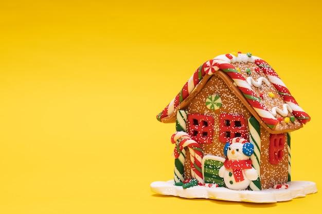 Casa giocattolo di natale con un pupazzo di neve su sfondo giallo