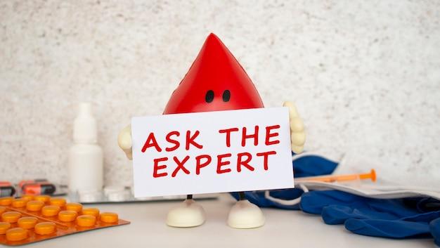 Una goccia di sangue giocattolo tiene un cartoncino bianco con la scritta ask the expert.