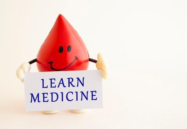 Una goccia di sangue giocattolo contiene un cartoncino bianco con la scritta learn medicine. concetto medico.