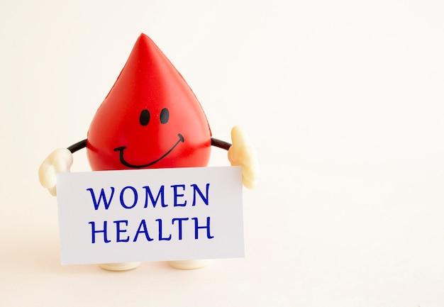 Una goccia di sangue giocattolo contiene una carta di carta bianca con la scritta women health.