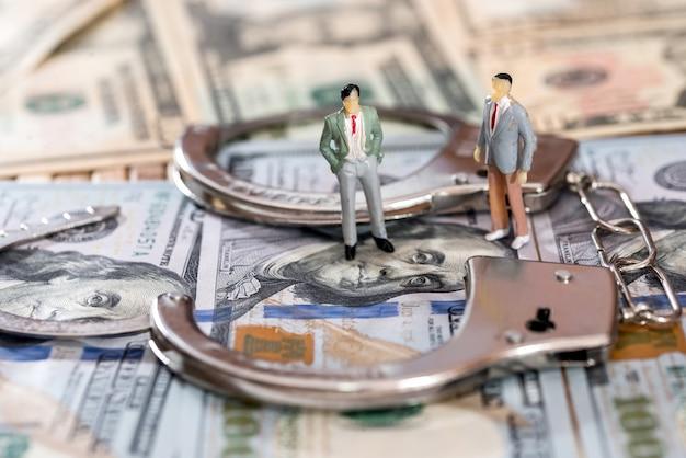 Figure del giocattolo con le manette sulle banconote del dollaro
