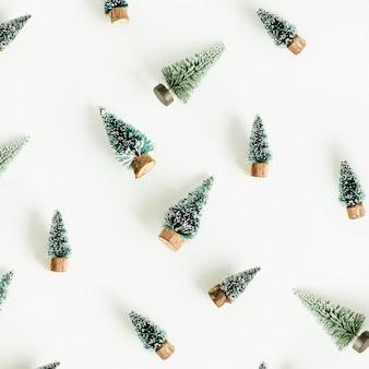 Modello di decorazione di abeti giocattolo su superficie bianca. vista piana laico e dall'alto