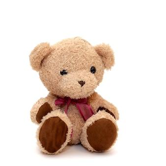Giocattolo simpatico orso carino con un fiocco rosso sul collo isolato su superficie bianca