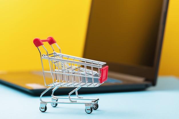 Carrello della spesa giocattolo sullo sfondo di un concetto di laptop sul tema dello shopping online