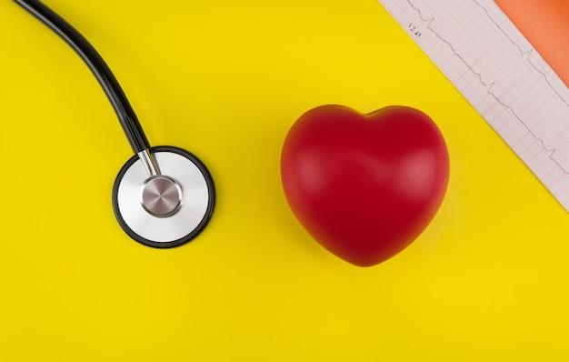 Cuore giocattolo e uno stetoscopio su sfondo giallo vista dall'alto cardiologia cura del cuore