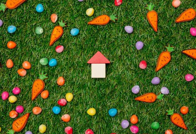 Casa del giocattolo e biscotti con le uova di pasqua su erba verde