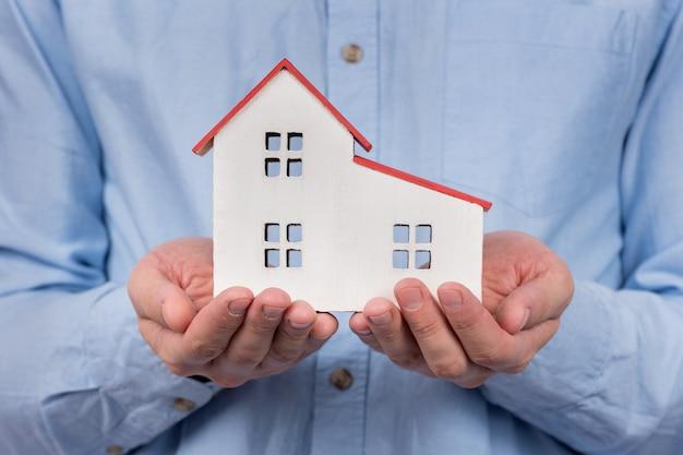 Modello di casa giocattolo in mani maschili. comprare casa, concetto di ipoteca