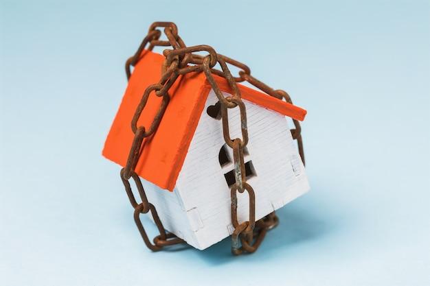 Casa giocattolo avvolta in una catena su un concetto di primo piano blu sul tema degli arresti di proprietà