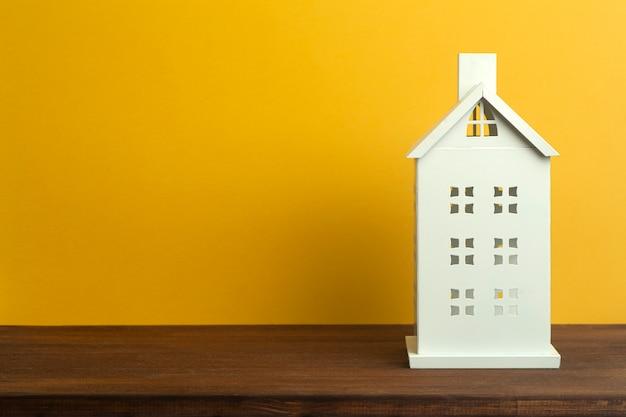 Casa del giocattolo su sfondo giallo. immobiliare, alloggi in affitto e concetto di casa.