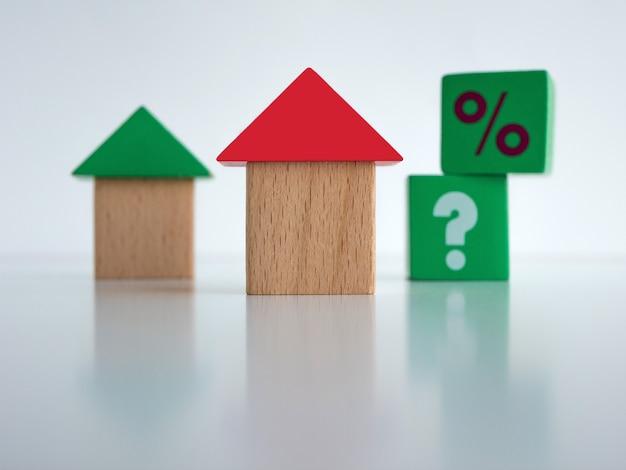 Case giocattolo fatte di cubi di legno con punti interrogativi e punti percentuali buing assicurazione ipotecaria e concetto di affitto
