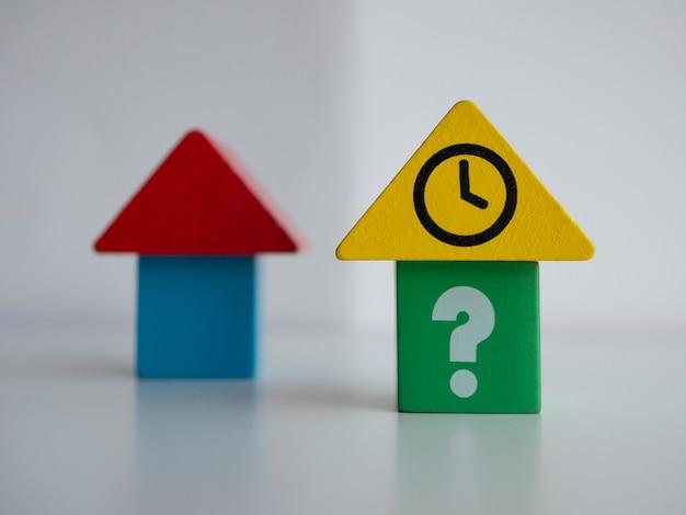 Case giocattolo con domande e segni di orologio. d tempistica di acquisto e affitto di assicurazione ipotecaria