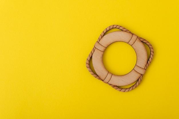 Salvagente giocattolo su sfondo giallo. concetto di sicurezza.