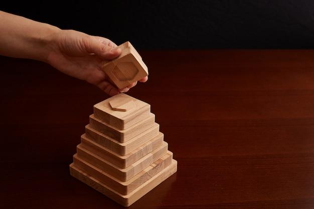 Giocattolo in legno di faggio. lavoro manuale sulla macchina cnc. piramide con forme geometriche. sviluppo, genitorialità e divertimento dei genitori